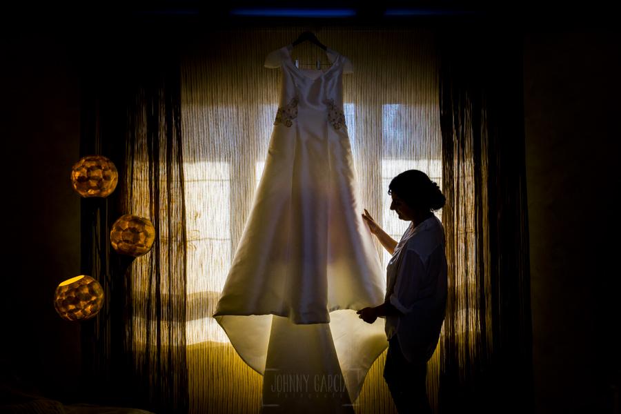 Boda en Íscar, Valladolid, de Marta y Oliver realizada por Johnny Garcia, fotógrafo de bodas en Valladolid, Marta junto a su vestido de novia