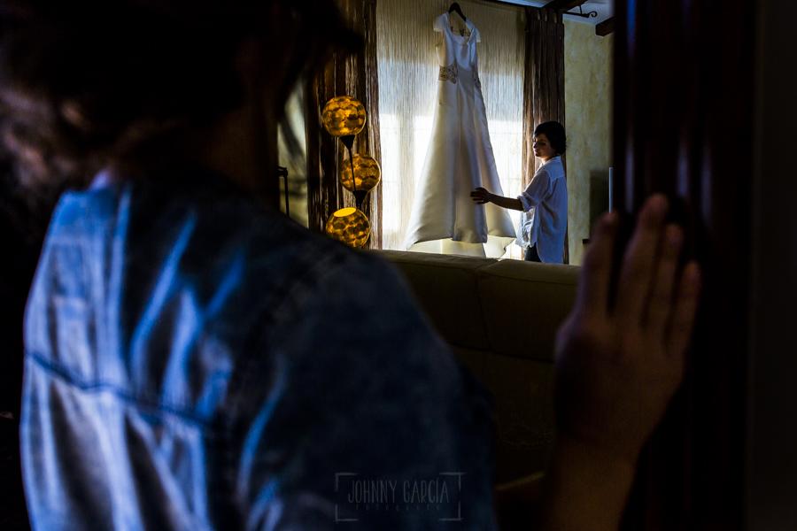 Boda en Íscar, Valladolid, de Marta y Oliver realizada por Johnny Garcia, fotógrafo de bodas en Valladolid, Marta prepara el vestido mientras la mira su hermana