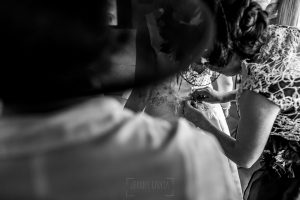 Boda en Íscar, Valladolid, de Marta y Oliver realizada por Johnny Garcia, fotógrafo de bodas en Valladolid, la hermana de Marta la abrocha el vestido de novia