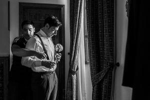 Boda en el Monasterio de Guadalupe de Ana Belén y Javier realizada por el fotógrafo de bodas en Extremadura Johnny García, el hermano de Javier le ayuda a ponerse los tirantes