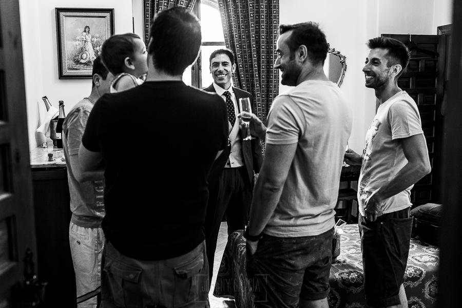 Boda en el Monasterio de Guadalupe de Ana Belén y Javier realizada por el fotógrafo de bodas en Extremadura Johnny García, Javier brindando con cava con sus amigos