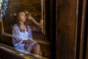 Boda en el Monasterio de Guadalupe de Ana Belén y Javier realizada por el fotógrafo de bodas en Extremadura Johnny García, un reflejo en una puerta de Ana Belén mientras se maquilla