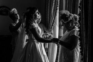 Boda en el Monasterio de Guadalupe de Ana Belén y Javier realizada por el fotógrafo de bodas en Extremadura Johnny García, últimos retoques a la novia por familiares