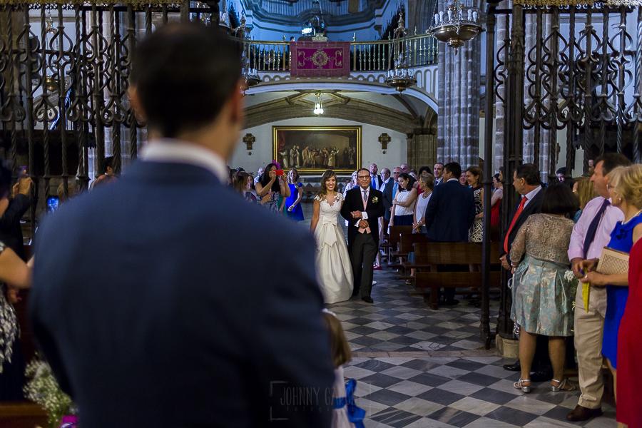 Boda en el Monasterio de Guadalupe de Ana Belén y Javier realizada por el fotógrafo de bodas en Extremadura Johnny García, Ana Belén llegando al altar, de espaldas Javier la espera