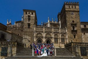 Boda en el Monasterio de Guadalupe de Ana Belén y Javier realizada por el fotógrafo de bodas en Extremadura Johnny García, foto de grupo de toda la boda en la fachada del Monasterio de Guadalupe