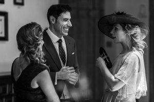 Boda en el Monasterio de Guadalupe de Ana Belén y Javier realizada por el fotógrafo de bodas en Extremadura Johnny García, Javier habla con invitadas durante el cóctail