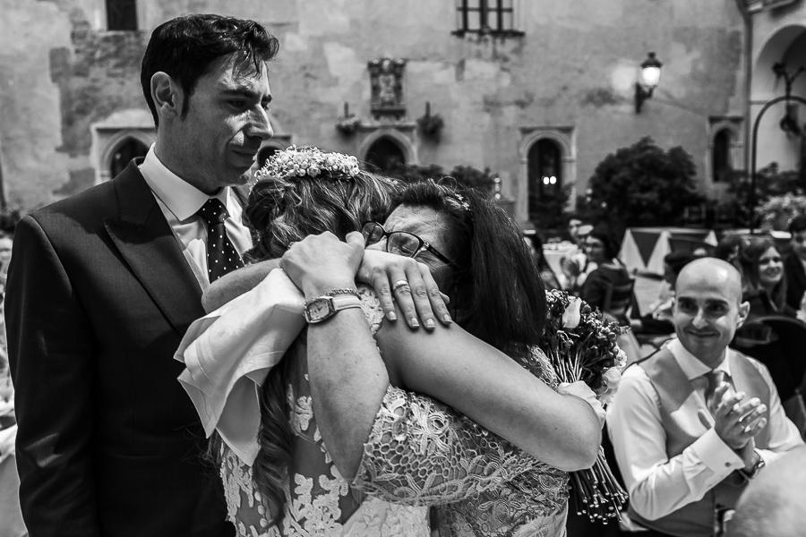 Boda en el Monasterio de Guadalupe de Ana Belén y Javier realizada por el fotógrafo de bodas en Extremadura Johnny García, la novia le regala el ramo de flores a su hermana