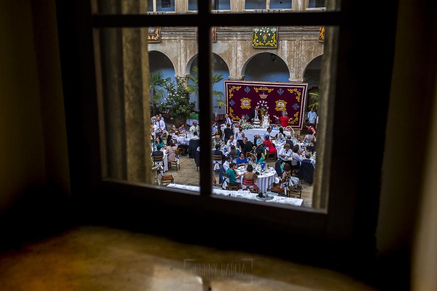 Boda en el Monasterio de Guadalupe de Ana Belén y Javier realizada por el fotógrafo de bodas en Extremadura Johnny García, vista del banquete a traves de una ventana