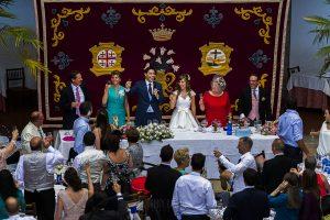 Boda en el Monasterio de Guadalupe de Ana Belén y Javier realizada por el fotógrafo de bodas en Extremadura Johnny García, la mesa nupcial brinda con todos los invitados