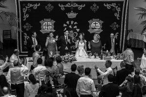 Boda en el Monasterio de Guadalupe de Ana Belén y Javier realizada por el fotógrafo de bodas en Extremadura Johnny García, la mesa de los novios brinda con todos sus invitados
