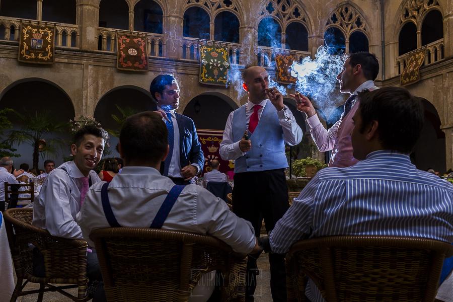 Boda en el Monasterio de Guadalupe de Ana Belén y Javier realizada por el fotógrafo de bodas en Extremadura Johnny García, amigos de los novios fumando puros