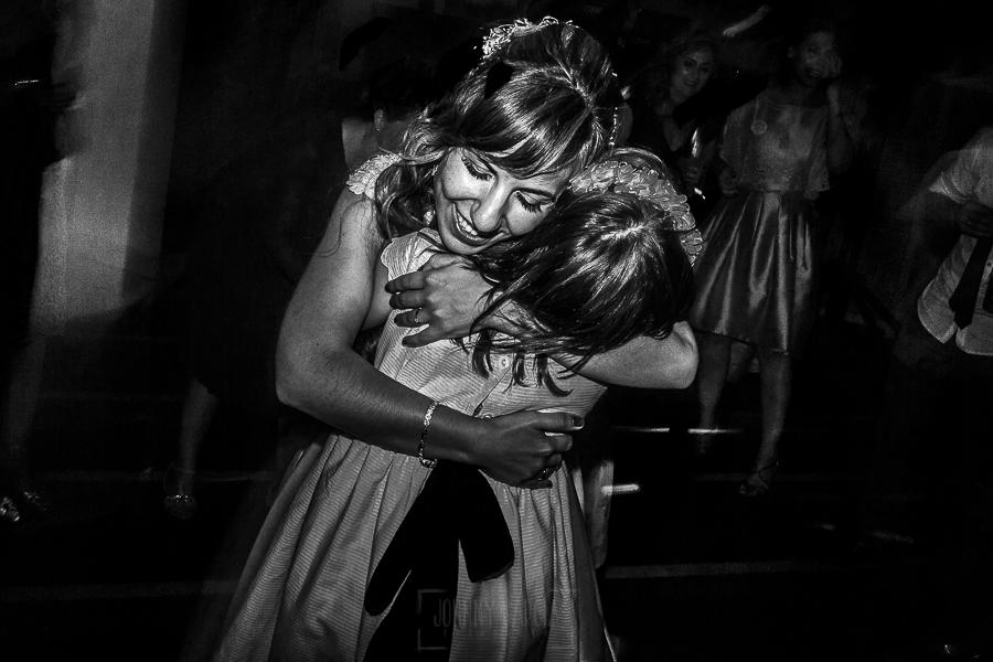 Boda en el Monasterio de Guadalupe de Ana Belén y Javier realizada por el fotógrafo de bodas en Extremadura Johnny García, la novia abraza a una sobrina