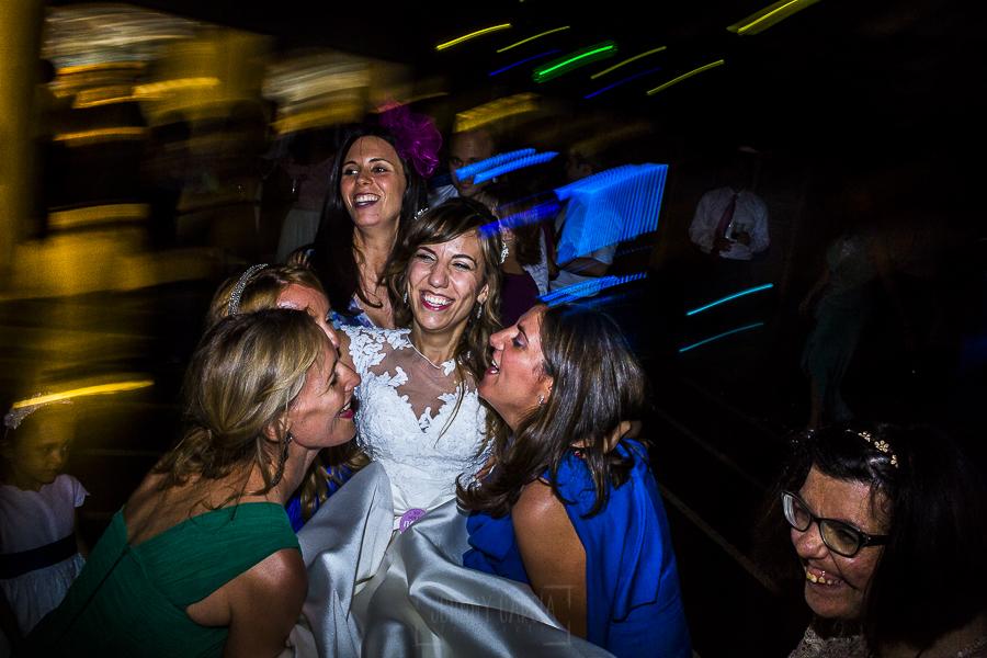 Boda en el Monasterio de Guadalupe de Ana Belén y Javier realizada por el fotógrafo de bodas en Extremadura Johnny García, las amigas de la novia intentan cogerla en el aire