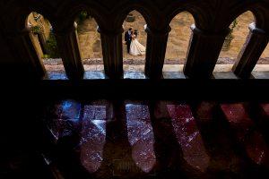 Boda en el Monasterio de Guadalupe de Ana Belén y Javier realizada por el fotógrafo de bodas en Extremadura Johnny García, un retrato de los novios a través de una barandilla de la hospedería