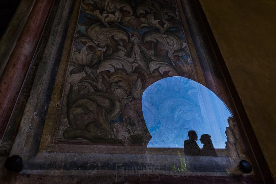 Boda en el Monasterio de Guadalupe de Ana Belén y Javier realizada por el fotógrafo de bodas en Extremadura Johnny García, un reflejo de la silueta de los novios en un cuadro