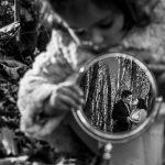 oda en el Torreón de Veredillas de María e Iván, fotos de boda realizadas por el fotógrafo de bodas en Cáceres Johnny García, la pareja reflejada en un espejo que sujeta Emma, foto destacada