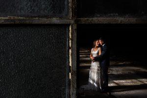 Bodas en Béjar, de Gema y Alberto realizada por el fotógrafo de bodas en Béjar, Salamanca, Johnny García, sesión de postboda en una fábrica textil de Béjar, una foto de la pareja a través de una ventana.