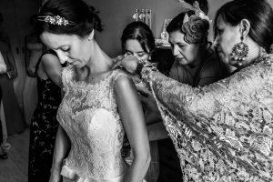 Bodas en Hervás, la boda de Laura y Carlos realizada por Johnny Garcia, fotógrafo de bodas en Extremadura, las amigas le ajustan el vestido a Laura