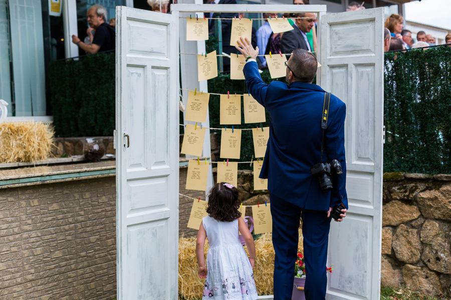 Bodas en Hervás, la boda de Laura y Carlos realizada por Johnny Garcia, fotógrafo de bodas en Extremadura, un invitado mira la distribución de las mesas