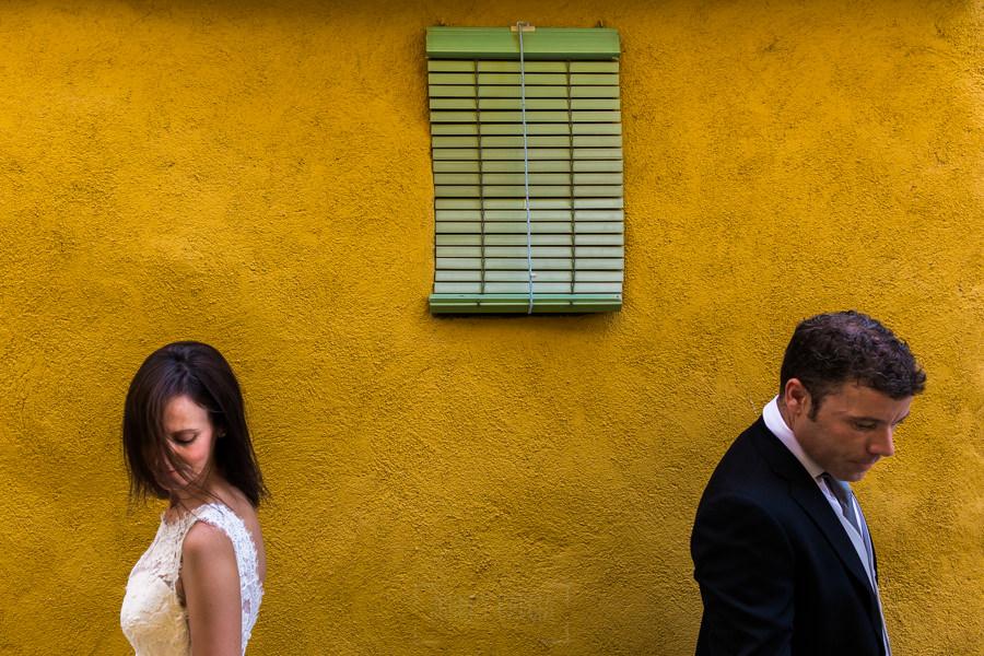 Bodas en Hervás, la boda de Laura y Carlos realizada por Johnny Garcia, fotógrafo de bodas en Extremadura, un retrato de Laura y Carlos delante de una fachada con un color llamativo