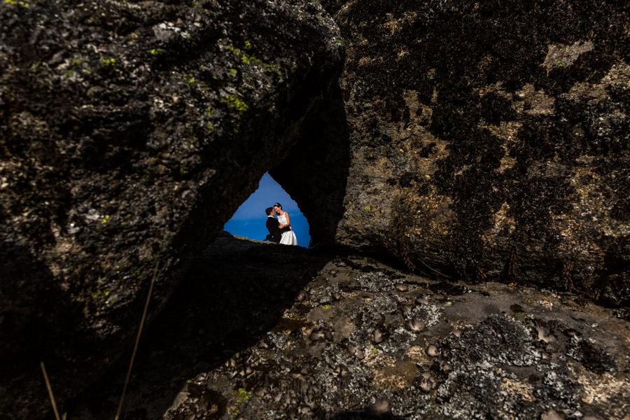 Bodas en Hervás, la boda de Laura y Carlos realizada por Johnny Garcia, fotógrafo de bodas en Extremadura, la pareja vistos a traves de un hueco en una roca