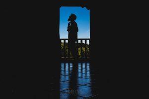 Boda en Puerto de Béjar de Ani y Hécter realizada por el fotógrafo de bodas en el Rincón de Castilla Johnny García, Salamanca; silueta del novio en el balcón del rincón de Castilla