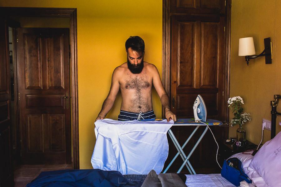 Boda en Puerto de Béjar de Ani y Hécter realizada por el fotógrafo de bodas en el Rincón de Castilla Johnny García, Salamanca; Hécter plancha su camisa.