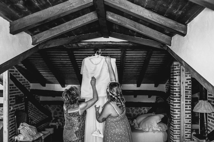 Boda en Puerto de Béjar de Ani y Hécter realizada por el fotógrafo de bodas en el Rincón de Castilla Johnny García, Salamanca; la novia y su madre preparan el vestido.