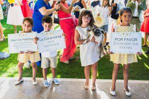 Boda en Puerto de Béjar de Ani y Hécter realizada por el fotógrafo de bodas en el Rincón de Castilla Johnny García, Salamanca; los pequeños con carteles.