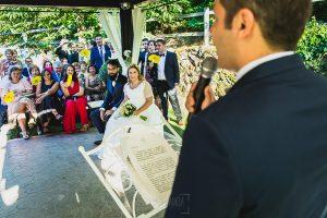 Boda en Puerto de Béjar de Ani y Hécter realizada por el fotógrafo de bodas en el Rincón de Castilla Johnny García, Salamanca; la pareja y un invitado leyendo.