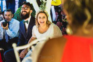 Boda en Puerto de Béjar de Ani y Hécter realizada por el fotógrafo de bodas en el Rincón de Castilla Johnny García, Salamanca; sonrisa de los novios mientras escuchan.
