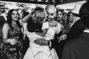 Boda en Puerto de Béjar de Ani y Hécter realizada por el fotógrafo de bodas en el Rincón de Castilla Johnny García, Salamanca; Ana abrazada por un familiar.
