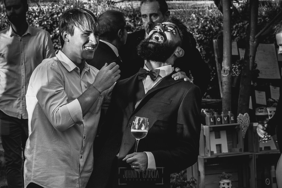 Boda en Puerto de Béjar de Ani y Hécter realizada por el fotógrafo de bodas en el Rincón de Castilla Johnny García, Salamanca; Hécter sonríe junto a un amigo.