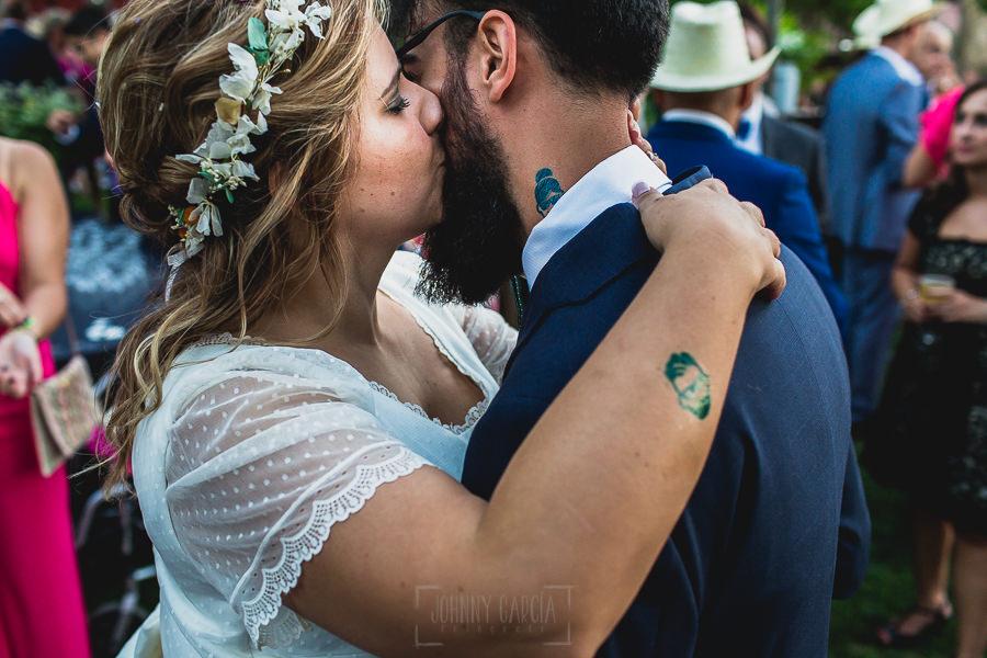 Boda en Puerto de Béjar de Ani y Hécter realizada por el fotógrafo de bodas en el Rincón de Castilla Johnny García, Salamanca; Ani besa a Hécter.