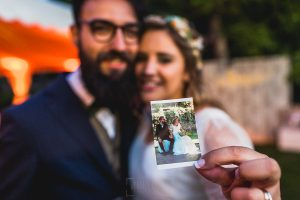 Boda en Puerto de Béjar de Ani y Hécter realizada por el fotógrafo de bodas en el Rincón de Castilla Johnny García, Salamanca; la pareja muestra una polaroid.