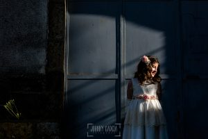 Comunión en Béjar de María, realizada por Johnny García, fotógrafo de comuniones en Béjar. María un retrato delante de una puerta azul.