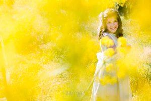 Comunión en Béjar de María, realizada por Johnny García, fotógrafo de comuniones en Béjar. María entre flores amarillas.