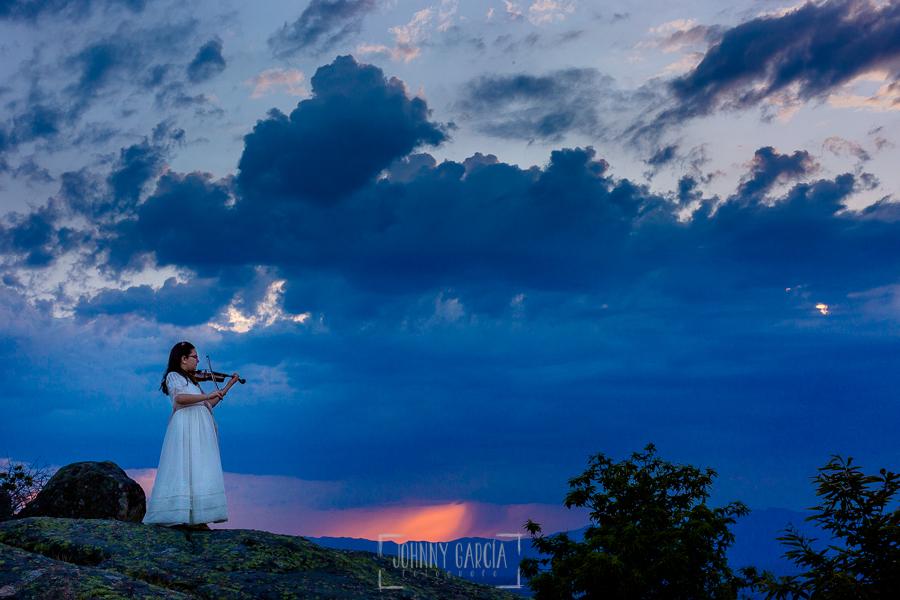 Comunión en Candelario de Lucia, realizada por Johnny García, fotógrafo de comuniones en Candelario. Lucia toca el violín ante la puesta de sol.