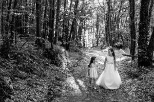Comunión en Hervás de Lia, realizada por Johnny García, fotógrafo de comuniones en Extremadura. Estela pasea junto a su hermana.