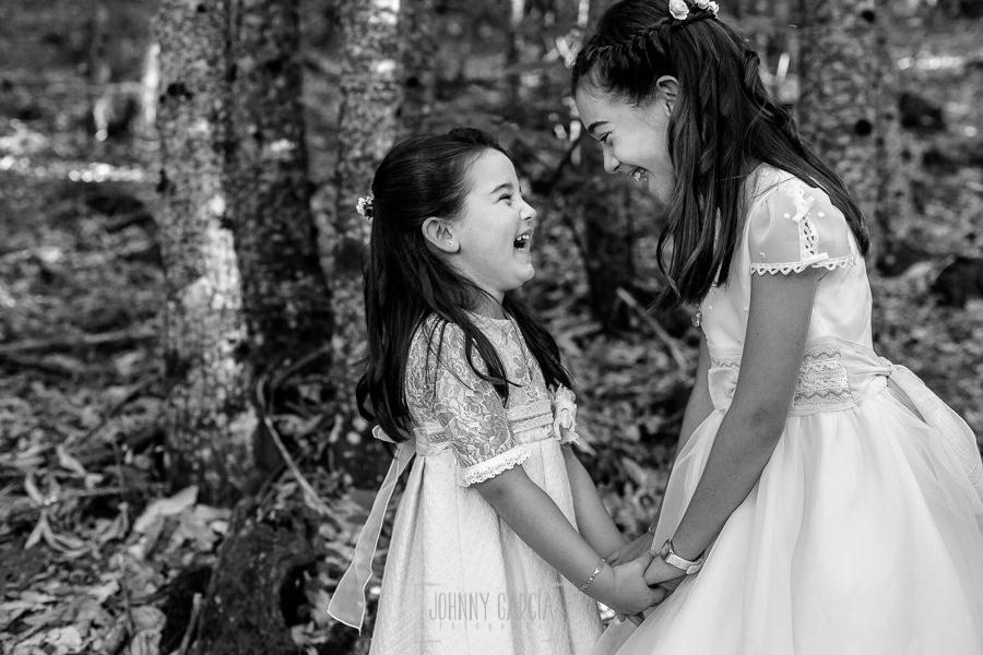 Comunión en Hervás de Lia, realizada por Johnny García, fotógrafo de comuniones en Extremadura. Estela ríe junto a su hermana.