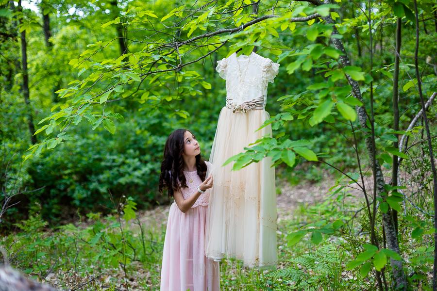 Comunión en Hervás de Karen, realizada por Johnny García, fotógrafo de comuniones en Extremadura. Karen junto a su vestido de comunión en el monte.