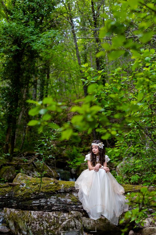 Comunión en Hervás de Karen, realizada por Johnny García, fotógrafo de comuniones en Extremadura. Karen sentada en un árbol caído en el monte.