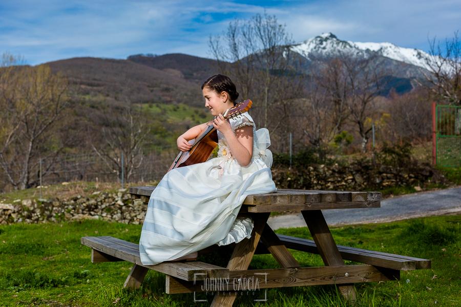 Comunión en Hervás de Sara, realizada por Johnny García, fotógrafo de comuniones en Cáceres. Sara sentada en una mesa tocando su guitarra.
