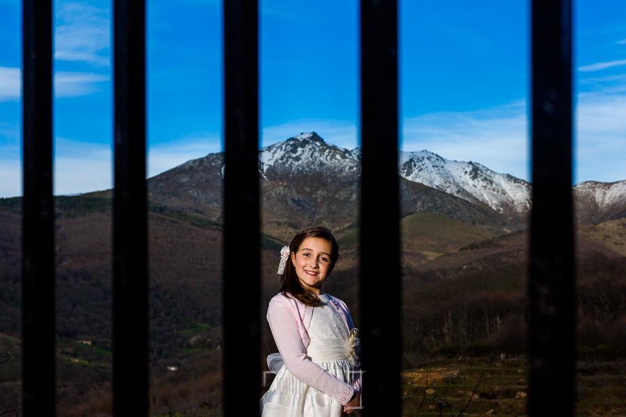 Comunión en Hervás de Sara, realizada por Johnny García, fotógrafo de comuniones en Cáceres. Sara detrás de una vaya.