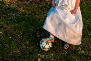Comunión en Hervás de Sara, realizada por Johnny García, fotógrafo de comuniones en Cáceres. Detalle del pie de Sara que tiene bota de fútbol y pisa un balón.