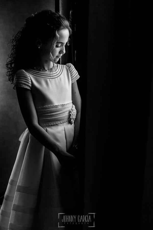 Comunión en La Alberca de Lia, realizada por Johnny García, fotógrafo de comuniones en Salamanca. Un retrato de Lia junto a una ventana.