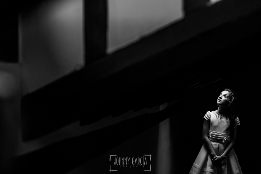 Comunión en La Alberca de Lia, realizada por Johnny García, fotógrafo de comuniones en Salamanca. Un retrato de Lia debajo de un hueco de luz.