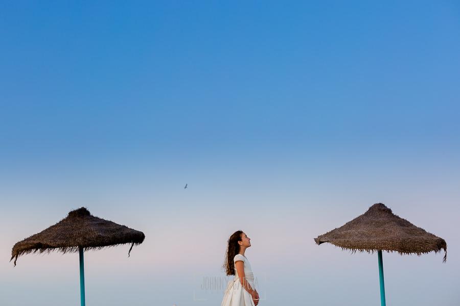 Comunión en Valencia de Lia, realizada por Johnny García, fotógrafo de comuniones en Valencia. Lia en la playa de Valencia entre dos sombrillas.