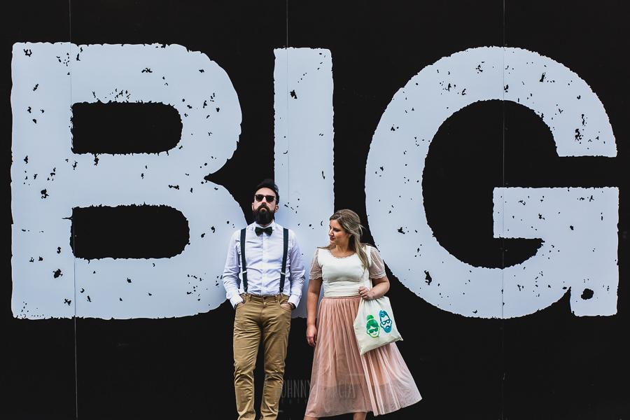 Post boda en Londres de Ani y Hécter realizadas por Johnny García, fotógrafo de bodas en Londres; retrato delante de un anuncio publicitario.