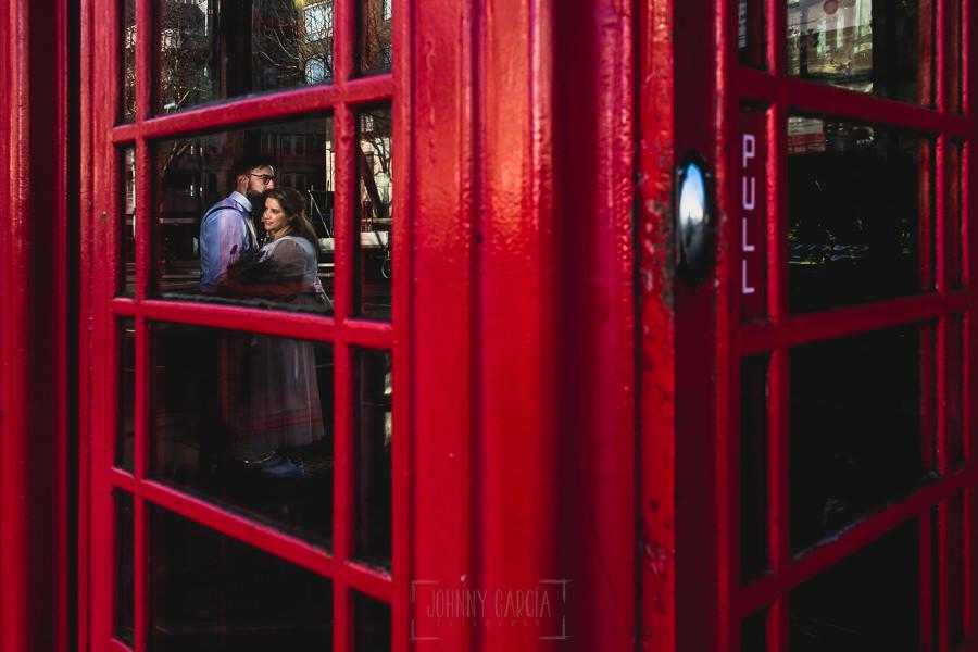 Post boda en Londres de Ani y Hécter realizadas por Johnny García, fotógrafo de bodas en Londres; los novios reflejados sobre el cristal de una cabina londinense.